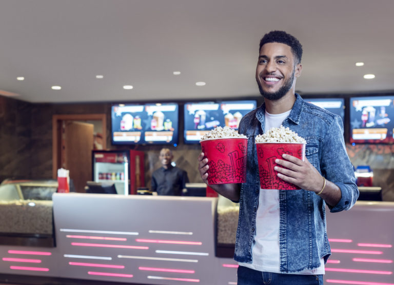 Mozambican model holds two popcorn packets, at the Gloria Mall cinema in Maputo, for the  Millennium BIM 2019 campaign, Dobra Mola.
